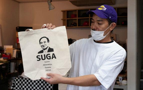 Designer Ippei Fujita displays a tote bag featuring Japan's expected new prime minister Yoshihide Suga at his store Marble in Yuzawa