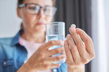 Mature middle-aged woman at home holding pill and glass of fresh water