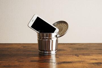 ゴミ箱に捨てられたスマートフォン