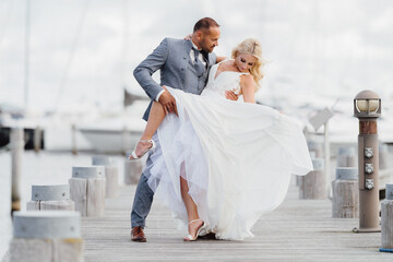 Happy just married couple dancing on the beach with yachts in the background. Wedding by the sea on the beach