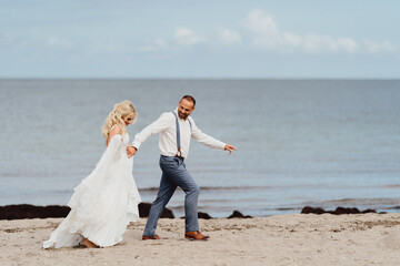 Happy newly married couple running on the beach. Wedding on the beach