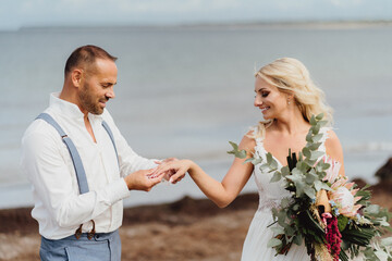 happy newly married couple exchange their wedding rings on the beach. Wedding on the beach