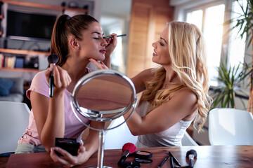 Female friends putting make up