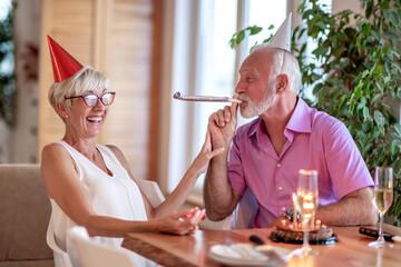 Senior couple celebrating birthday at home.