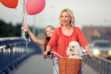 Mother and daughter having fun together,riding a bike.
