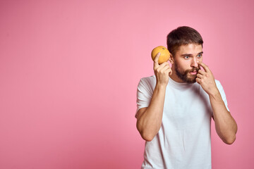 Young man with orange on a pink background in a white t-shirt emotions fun gesticulating with model hands