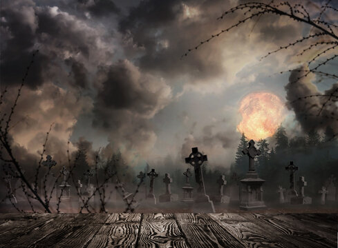 Wooden surface and misty graveyard with old creepy headstones under full moon on Halloween