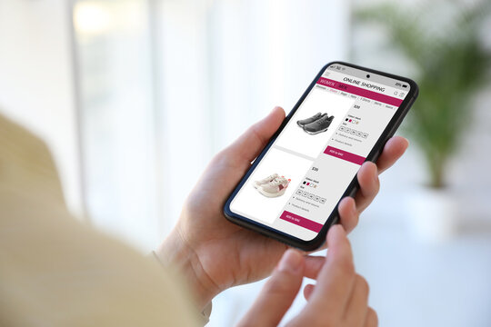 Woman shopping online via smartphone indoors, closeup