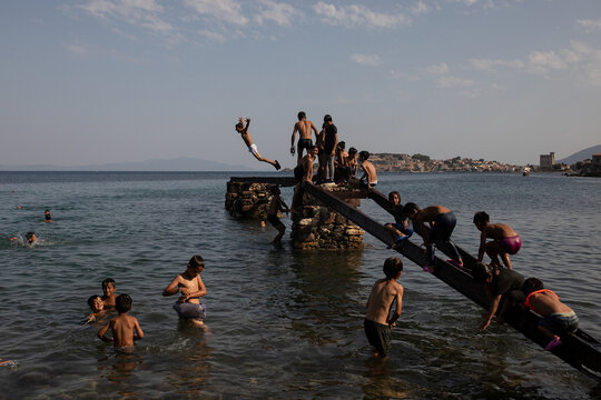 Children from the destroyed Moria camp for refugees and migrants dive to the sea from a platform, on the island of Lesbos