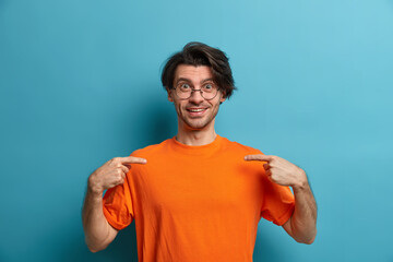Wall Mural - Happy adult man points at blank space of orange t shirt, gazes cheerful at camera and stands indoor against blue background. Handsome European guy shows his new casual outfit. Empty place for logo