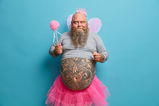 Indoor shot of funny dad entertains children on party, wears fairy costume with wings and holds magic wand. Plump bearded man animator poses against blue studio background. People holiday concept