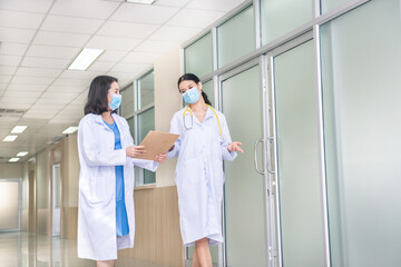 Two woman doctor with mask talking  in hospital corridor, health care.  female doctors examining a...