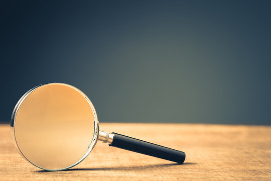Magnifying Glass on Wood Background