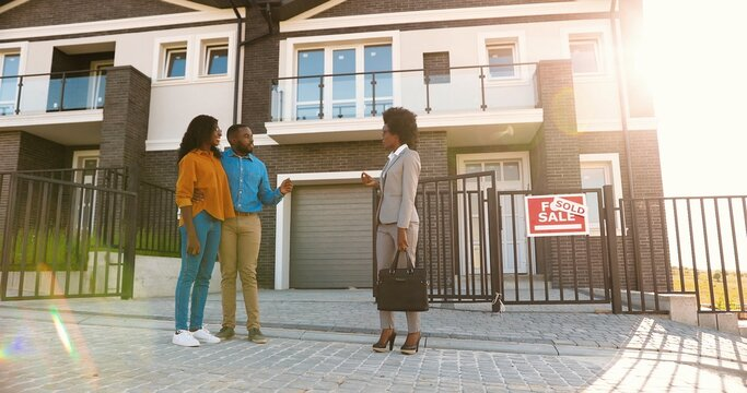 African American young woman real-eastate agent selling house to happy just-married couple. Outdoor. Wealthy man and woman buying dwelling in suburb. Businesswoman talking with new neighbors.