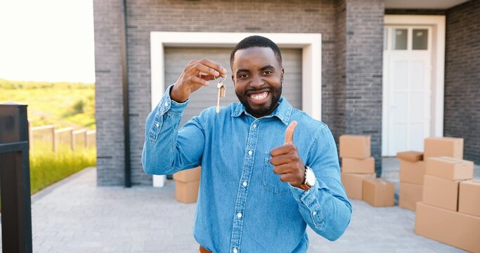 Portrait of cheerful happy African American man smiling to camera and showing key to camera while moving in new home. Outdoor. Male demonstrating keys. Carton boxes on background. Owner of real-estate