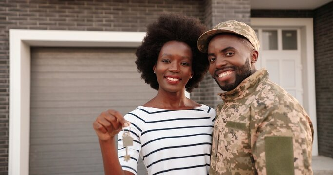 Portrait of young African American maried couple of army soldier standing in hugs outdoor at home, smiling and showing key to camera. Male officer in uniform with wife moving in new house. Real-estate