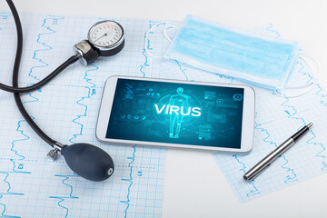 Tablet pc and doctor tools with VIRUS inscription, coronavirus concept