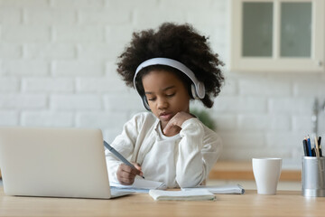 Focused little 7s mixed race child girl wearing wireless headphones, listening educational online lecture on computer, studying remotely writing notes in copybook, e-learning distant education concept