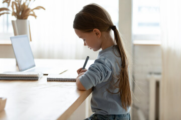 Foto auf Acrylglas Lineale Wachstum Side view focused small adorable caucasian girl sitting at desk with correct posture straight back, preparing homework alone indoors, smart little kid studying remotely, homeschooling concept.