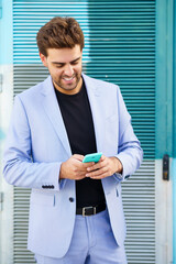 Young businessman wearing blue suit using a smartphone in urban background.