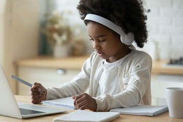 Concentrated little cute african american small child girl in modern wireless headphones sitting in...