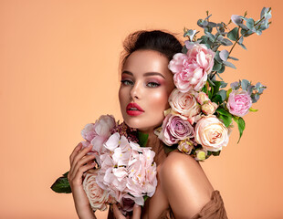 Attractive brunette girl with big beautiful  bouquet of  flowers. Beautiful white girl with flowers.  Pretty woman with bright makeup. Art portrait with flowers.
