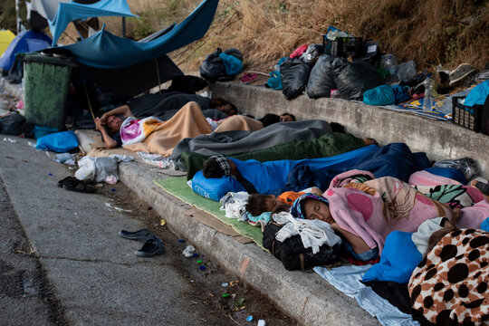 Refugees and migrants from the destroyed Moria camp sleep on the side of a road, on the island of Lesbos