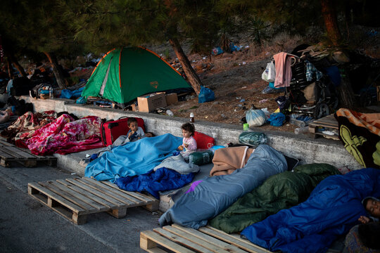 Two children eat cookies as refugees and migrants from the destroyed Moria camp sleep on the side of a road, on the island of Lesbos