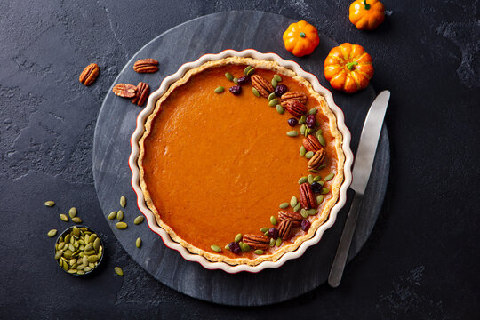 Pumpkin pie on marble board. Grey background. Close up. Top view.