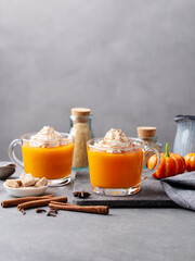 Pumpkin spice latte with whipped cream in glass cups. Grey background. Copy space.