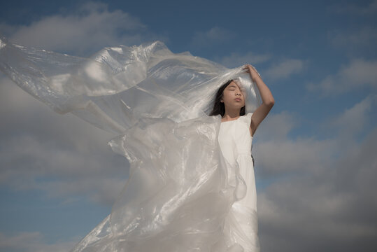 Teenage girl in white dress with plastic foil standing against cloudy sky