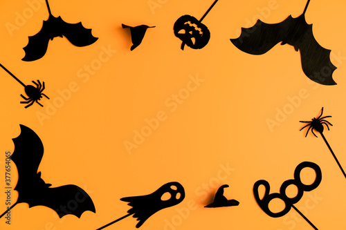 Happy Halloween day. Top view Halloween party accessories on orange background. Frame made of black halloween objects. Flat lay, copy space. Minimal style.