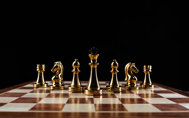 Golden chess figures standing on chessboard