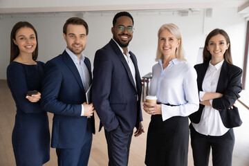 Portrait of smiling successful multiracial international businesspeople stand posing in office together. Happy motivated diverse multiethnic team show unity at workplace. Employment concept.