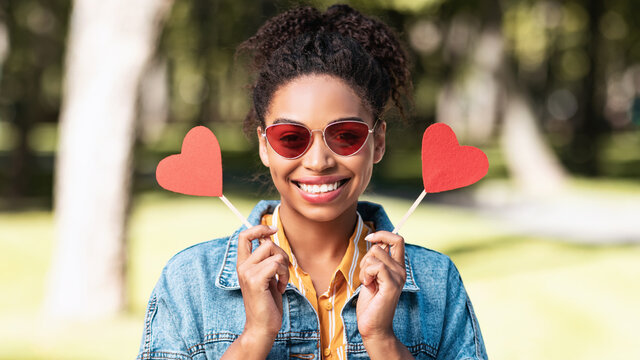 Black Girl Holding Two Paper Hearts Posing Standing In Park