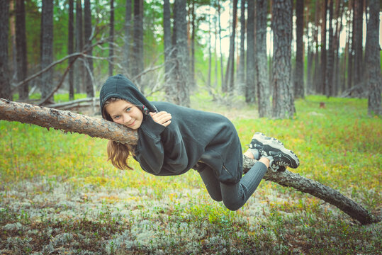 Brave girl in sweater with hood hanging on bent pine tree in the forest hugging her.