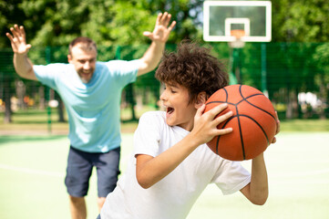 Excited dad playing basketball with his son outdoors