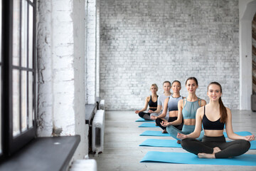 Group of women in the gym practice yoga, lotus position.
