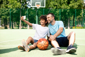 Happy dad and son taking selfie using smart phone