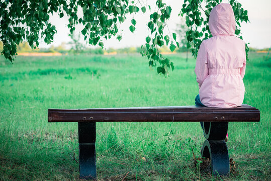 Lonely girl in summer jacket with hood is resting on bench under green birch.