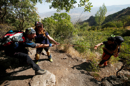 Iraqi Kurdish hikers use a rope to pull a fellow hiker as they walk on Safin mountain in Erbil