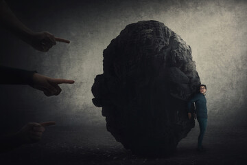 Scared businessman hiding behind a huge boulder, feels discomfort as people hands pointing to him blaming as guilty. High tension, person under pressure, emotional stress. Man social victim concept.