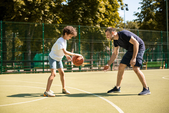Sportive man teaching boy how to play basketball