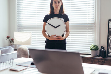 Woman in office with large wall clock.