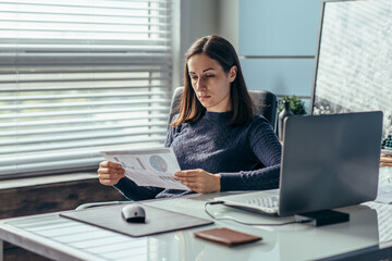 Woman works with documents in the office.