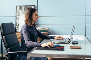 Woman with laptop at desk working or studying online.