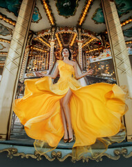 Young beautiful woman in a bright yellow evening dress posing against the backdrop of an amusement park and carousel