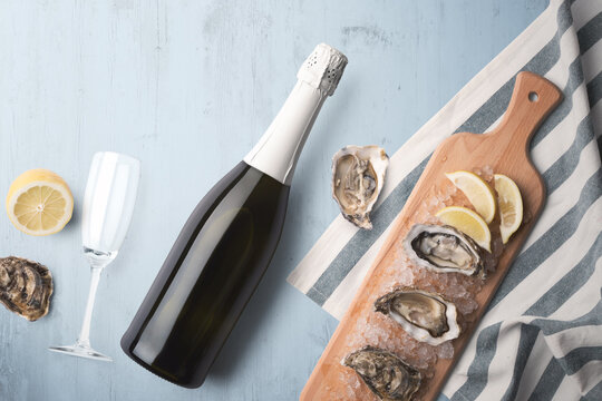 An unopened champagne bottle with a single glass on a blue tinted wooden background with fresh oysters and lemon on a wooden cutting board