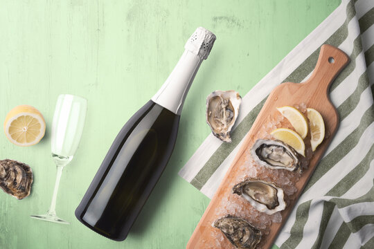 An unopened champagne bottle with a single glass on a green tinted wooden background with fresh oysters and lemon on a wooden cutting board