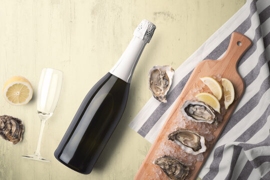 An unopened champagne bottle with a single glass on a yellow tinted wooden background with fresh oysters and lemon on a wooden cutting board